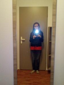 Une femme appuyée sur une porte de couleur beige, se prend en photo par le biais d'un miroir. Le flash de la caméra provoque un artifact et une tache de lumière de taille non-négligeable apparaît à l'endroit de l'appareil photo.
