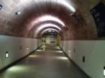Tunel faiblement illuminé. La voute est arrondie, les murs sont blancs en bas et rougeâtres en haut.